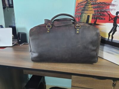 Custom made unisex duffle bag made from dark brown leather within custom made realization