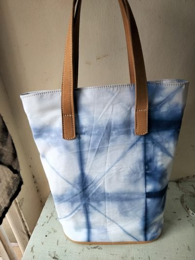 Custom made tie-dye fabric bag with brown leather straps within custom made realization